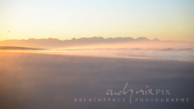 Mist rising from the sand and waves on a Muizenberg Beach Sunrise