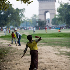 Boys play cricket in the park at India Gate
