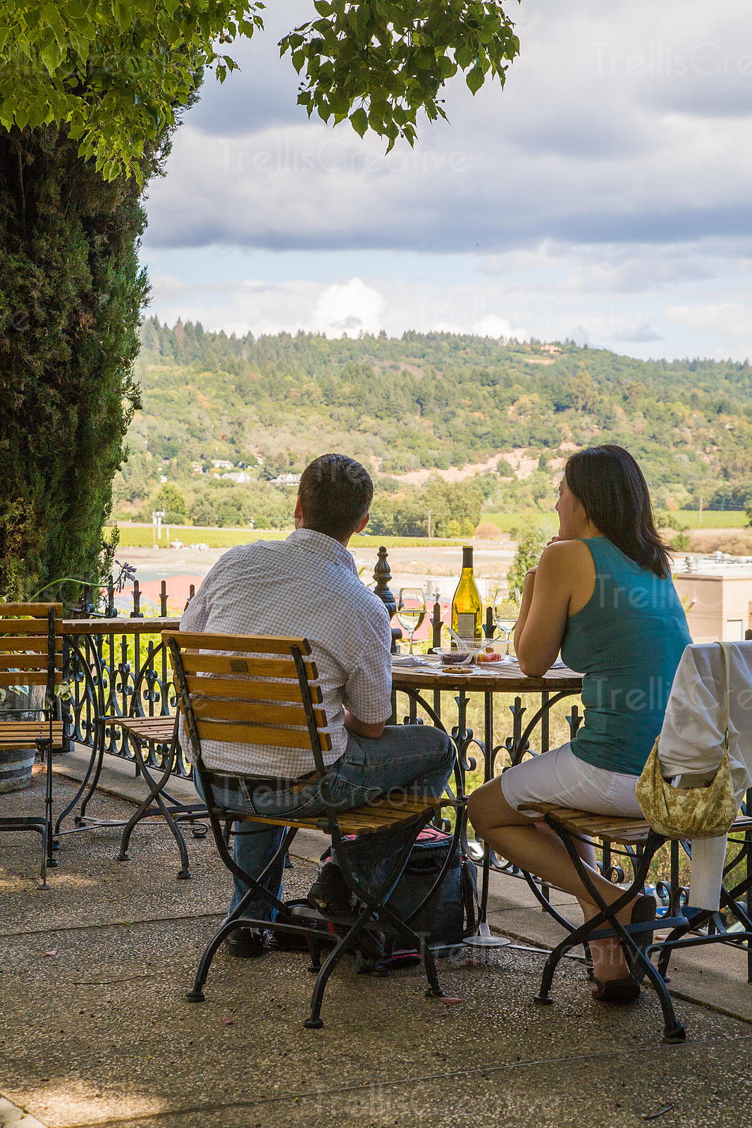 A young couple enjoy dinner outside overlooking the Napa Valley