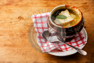 Authentic French Onion soup with dried bread and cheddar cheese in bowl on wooden background copy space