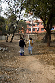 India - Delhi - A nurse leads a patient through the grounds for therapy at the Department of Psychiatry