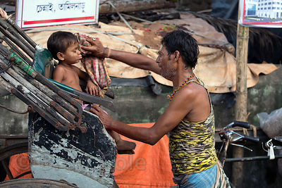 An auto rickshaw driver shares a moment with his son, Strand Bank Road, Kolkata, India