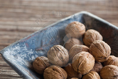 walnuts in shells nestling in a blue square ceramic dish, on woven mat, close up