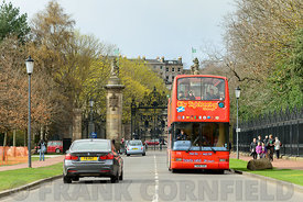 EDINBURGH, SCOTLAND – APRIL 16, 2016: Tourist sightseeing bus tour of landmarks in the city of Edinburgh, Scotland.  The bus is at the entrance to Holyrood Park.