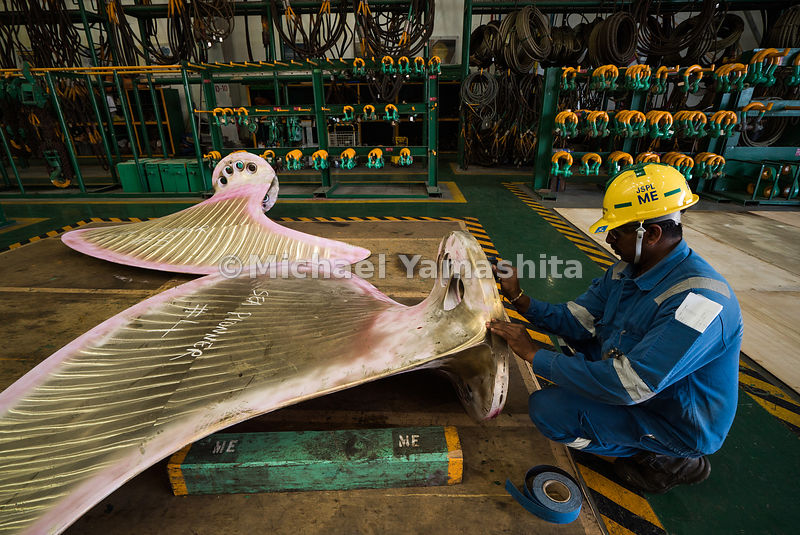 An employee of Semcorp Marine, another major force in the offshore and marine sector, marks a ship propeller for easy identification during repairs.