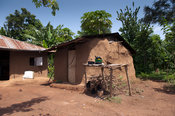 Mud hut home in rural Kenya, with cooking equipment outside.