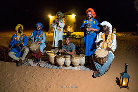 Musicians perform near a biouvac tent setup in the sand dunes of Erg Chebbi in Sahara Desert, Morocco