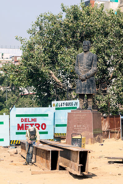 India - Delhi - A worker spot welds metal by the Metro construction at Kashmere Gate next to a statue of Asif Ali,