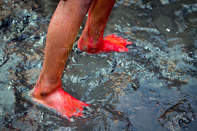A boy's feet are covered in orange gulal powder during immersion of Ganesh idols in the Yamuna River during the Ganesh Chaturthi festival, Delhi, India