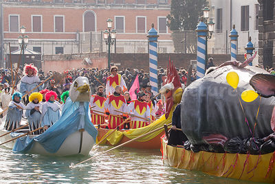 People wearing colourful Costumes heading up the Venice Carnival Water Parade