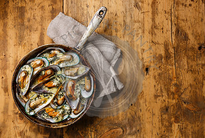 Mussels Clams Kiwi in Blue cheese sauce in cooking pan on wooden background copy space