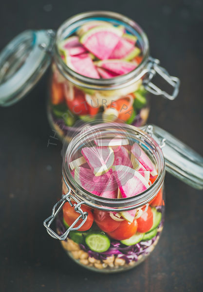 Vegetable, chickpea sprout salad in jars, dark scorched wooden background