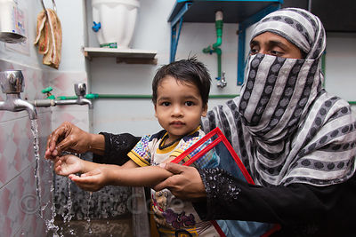 A mother washes her son's hands before eating at a health clinic Howrah, India