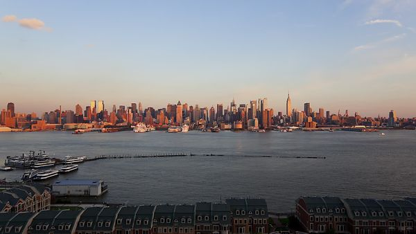 Wide Shot: Cruise Ships Leaving Port As Manhattan Switches On For The Night