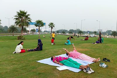 India - New Delhi - Women practice yoga on the private traffic greens at Aerocity near Terminal 3 of Indira Gandhi Airport,