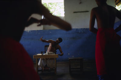 India - Kerala - Boys practice at dawn under the instruction of a master teacher at a dance class