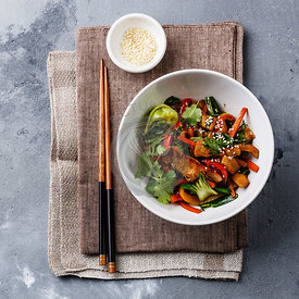 Chicken meat with vegetable in bowl stir fry on wok on concrete background