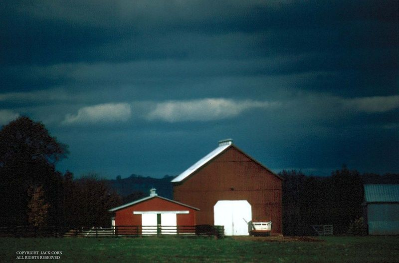 Red barns and dark sky