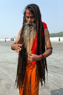 A sadhu (holy man) adjusts his waist-length dreadlocks at the Gangasagar Mela, a Hindu pilgrimage to Sagar Island in the Bay of Bengal in India, where the Ganges meets the sea.