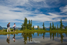 Two day hikers doing the Perry Creek–Mt. Forgotten Measdows Trail, with Glacier Peak viewed from a tarn in Mt. Forgotten Meadows, Mt. Baker-Snoqualmie National Forest, Cascade Mountains, Washington, USA, August, 2008_WA_4578