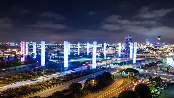 Medium Shot: Heavy Traffic, Wispy Clouds, & The 13 Neon Pylons of LAX