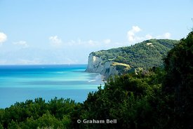 cliffs with albanian mountains in the distance from san stefanos, north west corfu, ionian islands, greece