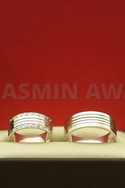 Elegant wedding rings with red background and copy space for text or invitation..Studio Shot