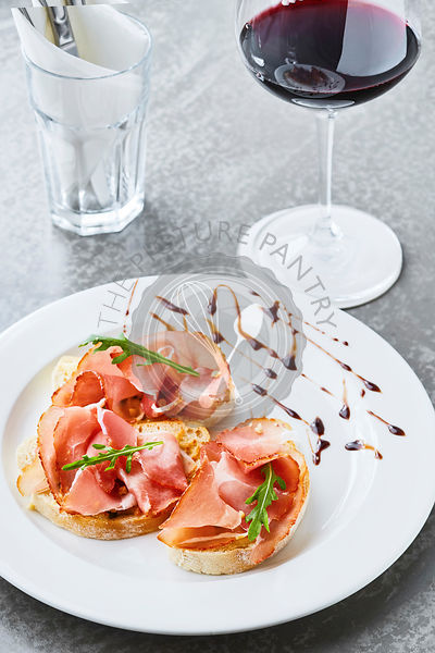 Bruschetta with Parma Ham and Pine Nuts and a glass of wine on concrete table