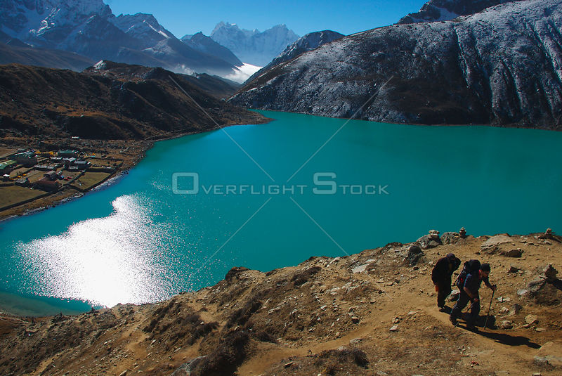 NEPAL Gokyo Peak -- A trekker and his guide ascend Gokyo Ri (Gokyo Peak) with the third lake of the spectacular Gokyo valley in the background.