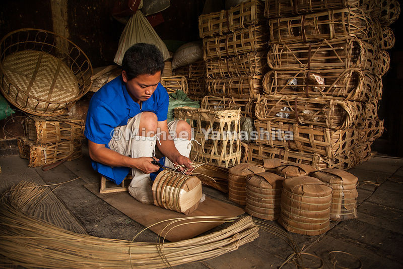 Packing puer tea for shipment in Menghai - seven tea cakes are fitted into Bamboo-Shoot husk wrappers. Horses and mules once would each carry four baskets loaded with six of these packages.