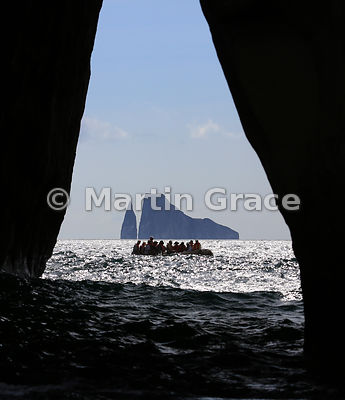 Looking through an arch in Cerro Brujo to a tourist Zodiac inflatable and Kicker Rock beyond, San Cristobal, Galapagos
