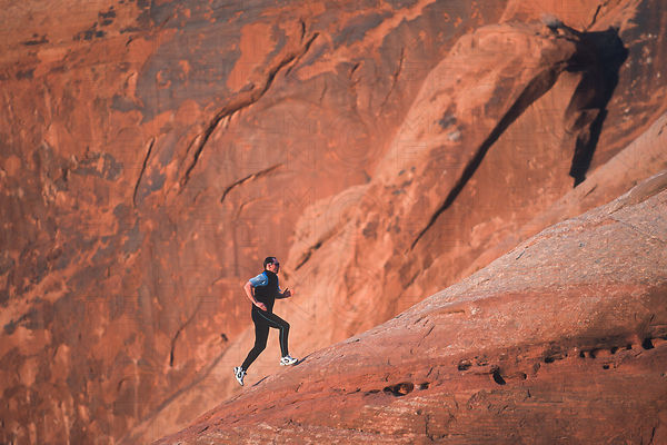 solo man running uphill on slickrock moab utah usa
