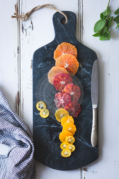 Citrus fruits on a marble chopping board.