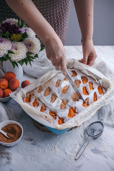 Woman slicing baked apricot yogurt cake in a baking pan on a white marble table