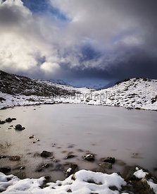 Storm clouds over a frozen Loch Allt an Daraich with the summit of Creag Dhubh in the distance. Scottish Highlands, Scotland, UK.