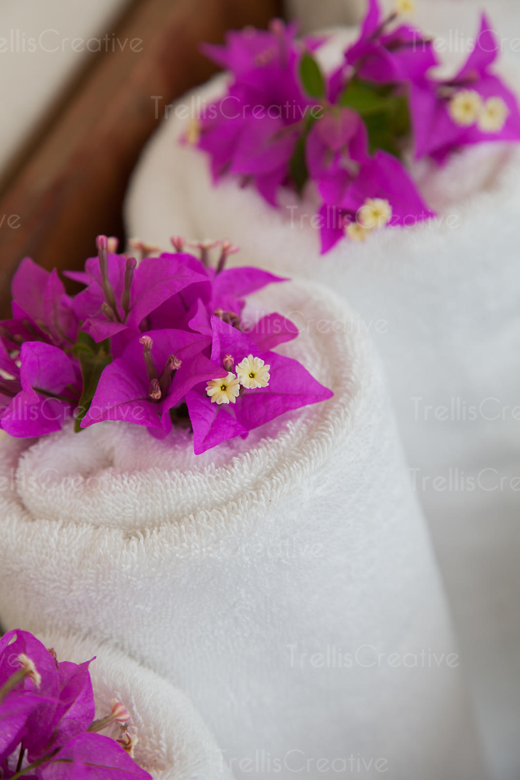 Accents of bougainvillea flowers on fresh white towels at the spa