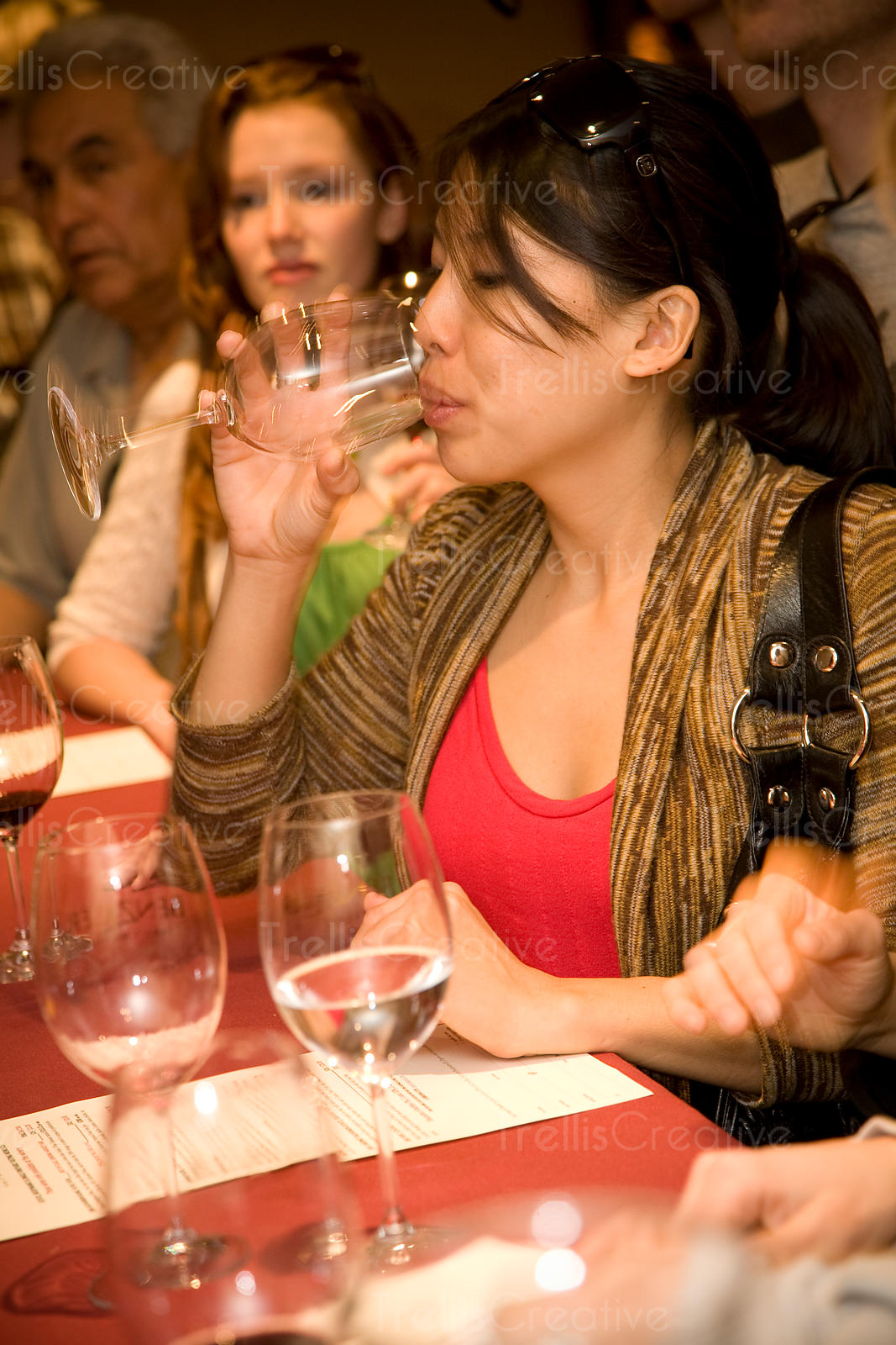 A young Asian woman drinks wine in a winery tasting room