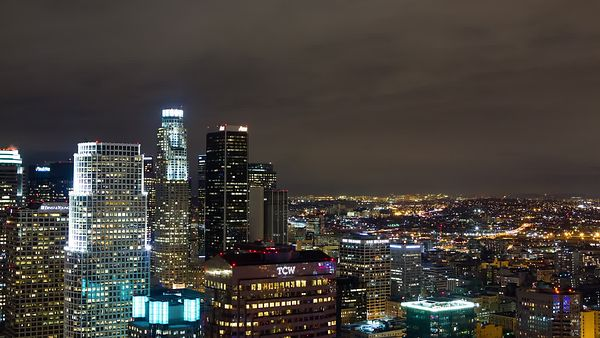 Bird's Eye: A-slanted Pan Of Los Angeles Skyline Under A Low Deck Of Clouds At Night