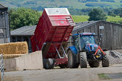 New Holland four wheel drive tractor with a Marshall silage trailer unloading a load of silage in a farm yard at harvest time, Cumbria, UK.