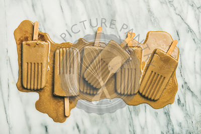 Flatlay of melting coffee latte popsicles over grey marble background, top view, horizontal composition