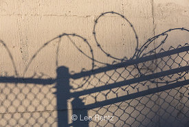 Shadows of Razor Wire Topping Chain Link Fence in Seattle