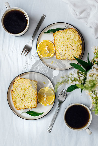 Lemon zucchini bread slices served on two plates with a lemon slice on the side. Two cups of coffee, two forks and flowers in a vase accompany.