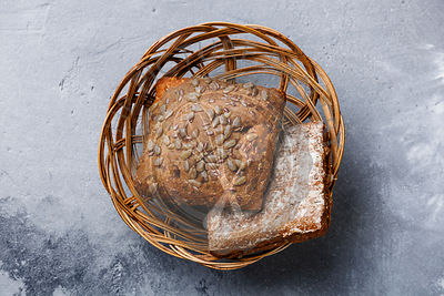 Fresh cereals bread bun with sunflower seeds in Wicker basket on grey concrete background