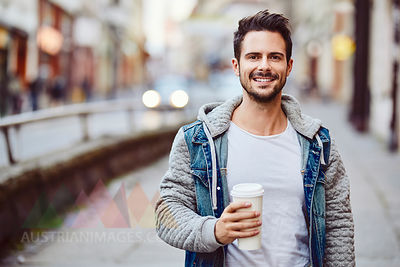 Portrait of smiling man holding coffe with city street in backgorund