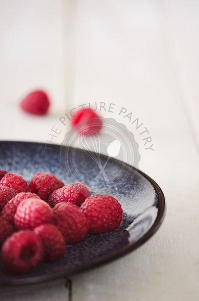 Raspberries on Plate on White Background