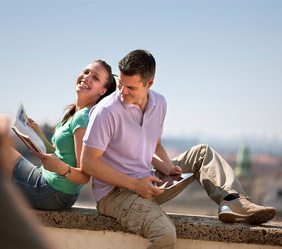 Woman and man sitting on wall