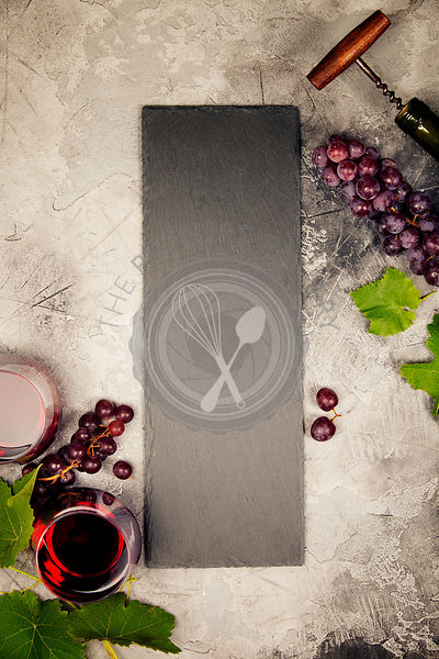 Top view of a blank chalk board for a wine list or menu with Wine and snack set. Variety of cheese, olives, prosciutto meat, baguette slices, black grapes and glasses of red wine over grey marble background, top view, copy space