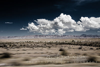 White cumulus clouds over distant mountains, flat desert scrub, motion blurred in foreground