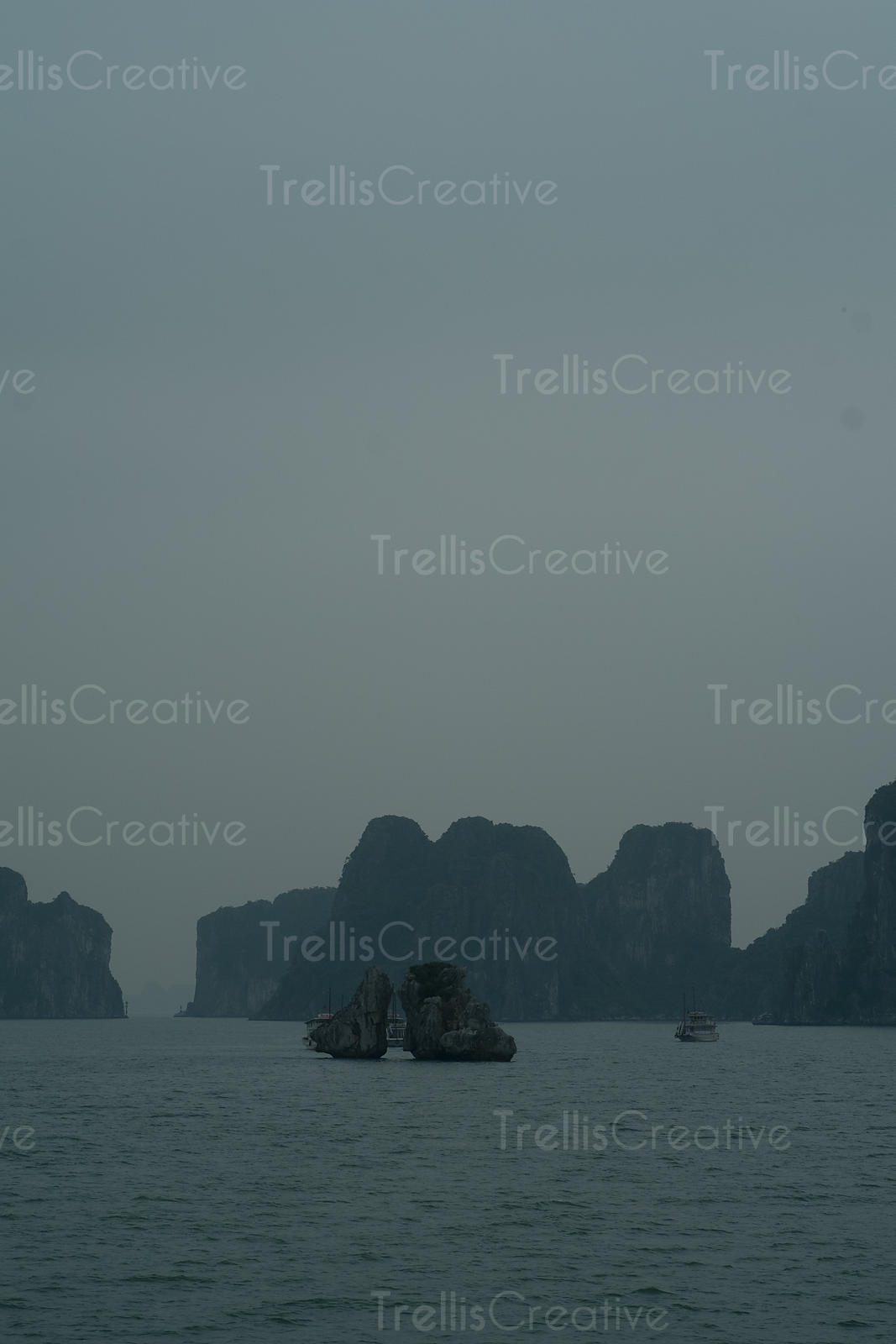 Tourboat sailing between the limestone cliffs in Halong Bay, Vietnam