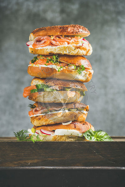 Heap of Bagels with salmon, eggs, vegetables, capers, fresh herbs and cream-cheese, grey concrete background